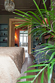 Potted palm and bed in bedroom with open door