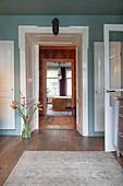Floor vase of amaryllis next to white door frame in blue wall