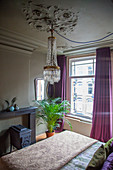 Chandelier above double bed, cast iron stove and potted palm in bedroom