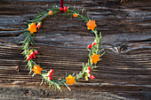 Scented wreath of rosemary branches decorated with shapes cut out of orange peel
