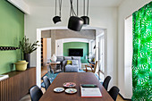 Elegant walnut table and sideboard in dining room with green accent wall