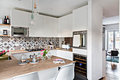 White fitted kitchen with decorative cement tiles and dining table