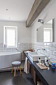 Washstand and free-standing bathtub in bathroom with subway tiles