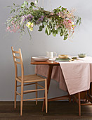 Wreath of flowers suspended over dining table