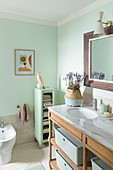 Washstand with marble top and shelves in bathroom with mint-green walls