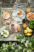 Fruit and pastries on breakfast table in garden