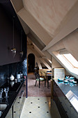 Modern black fitted kitchen in attic room