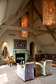 Seating area with fireplace, chandelier and artworks in attic room