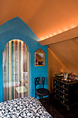 Kommode vor blauer Wand und Türvorhang im Schlafzimmer