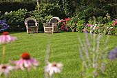 Rattan armchairs next to flower bed in garden
