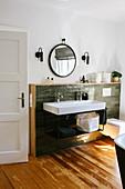 Waschbecken mit zwei Armaturen vor grünen Wandfliesen mit Holzumrahmung