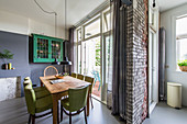 Wooden table and green chairs next to balcony doors