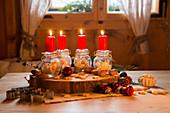 Vier rote Kerzen auf Einmachgläsern mit Plätzchen als Adventskranz