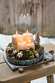 Four white pillar candles, moss and decorations on metal tray