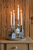 Advent arrangement of four white tapered candles in swing-top bottles