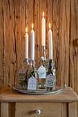 Vier weiße Stabkerzen in Bügelflaschen als Adventskalender