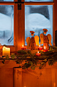 Arrangement of cinnamon-stick angels and candles in rustic window