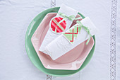 Embroidered tags on linen napkins on pastel plates