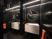 Modern bathroom with black mosaic tiles and mirrored wall