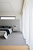 Modern bedroom in pale grey with panelled walls