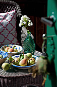 Pears in rustic ceramic bowls and white phlox in glass bottle