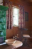 Alter Drehstuhl am Fenster neben klassischem Kachelofen in der Stube