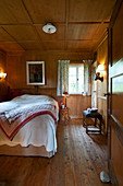 Country-house-style bedroom with panelled walls and coffered ceiling