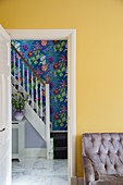 View of staircase in hallway with marble floor and floral wallpaper