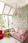 Pink sofa against wallpaper with bird motif in girl's bedroom