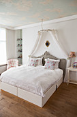 Double bed with bed crown in bedroom