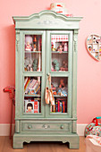 Antique glass-fronted cabinet in girl's bedroom
