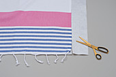 Striped cloth, oilcloth and scissors