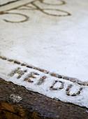 Selbstgemachte Schrift aus Kieselsteinen im Betonboden