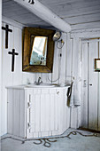 Corner sink with white, fitted wooden surround in rustic, country-house-style bathroom