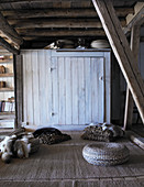 Floor cushions, fur blankets and pouffe in old, rustic wooden house