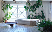 Fur blanket on couch in bright room with wooden floor and many houseplants