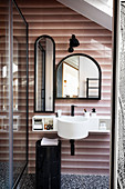 A view into a bathroom with a hand basin and mirrors