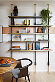 An open bookshelf with a round wooden table and a designer chair in front of it