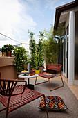 Outdoor-Sessel und Tisch auf PVC-Teppich auf der Terrasse