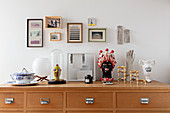 Decorative objects on a chest of drawers with framed pictures above it