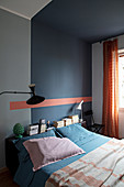 A double bed in a bedroom with a dark wall
