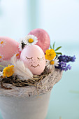 Pot as Easter basket, Easter egg with face, daisies, buttercups, grape hyacinth and feather as decoration