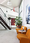 Orange chairs and a side table in a loft apartment with stairs in the background