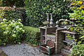 A brick outdoor kitchen in front of a hedge in an autumnal garden