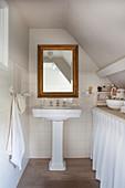 A nostalgic attic bathroom with a gold-framed mirror
