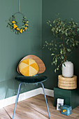 Yellow velvet cushion on retro chair against dark green wall