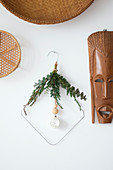 Bent metal coat hanger decorated with twigs on wall next to ethnic mask