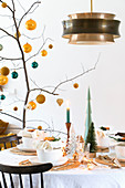 Branch decorated with yellow and petrol baubles on set table