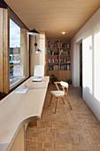 Langer Schreibtisch im schmalen Arbeitszimmer in hellem Holz