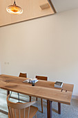 Wooden table and various chairs in minimalist dining room